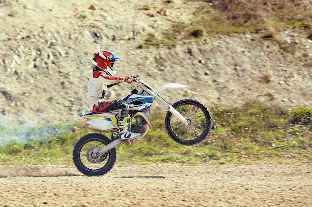 Водитель мотокросса в действии, ускоряя мотоцикл, взлетает и прыгает на трамплин на гоночной трассе.