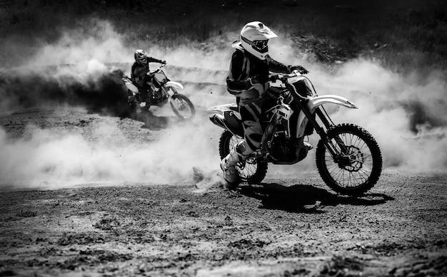 Гонщик мотокросса ускоряется на пыльной трассе черно-белое высококонтрастное фото