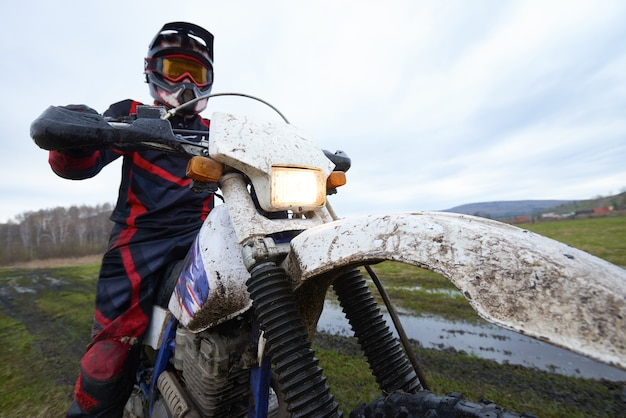 Motocross racing in the countryside with professional biker against cloudy sky