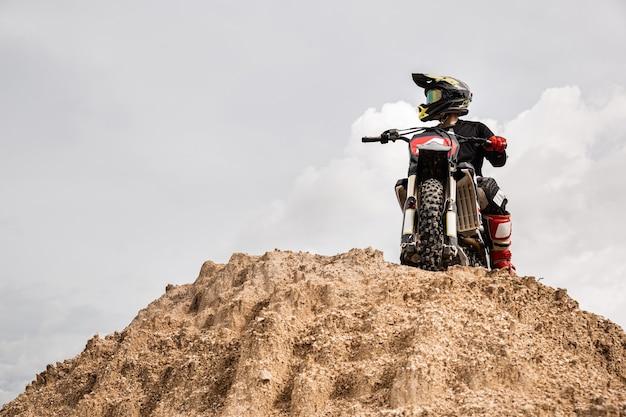 ダートトラック、エクストリームスポーツ、トラベルアドベンチャーのコンセプトでレースをする準備ができているバイクのモトクロスライダー。