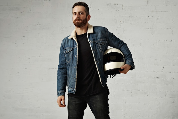 Motor biker wears shearling denim jacket and black blank henley shirt, holds vintage beige motorcycle helmet, isolated in center of white brick wall