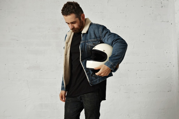Motor biker wears shearling denim jacket and black blank henley shirt, holds vintage beige motorcycle helmet, looking down, isolated in center of white brick wall