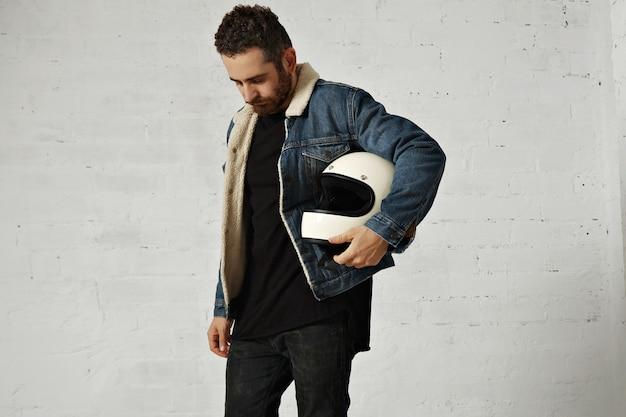 Motociclista indossa giacca di jeans shearling e camicia henley nera vuota, tiene il casco da motociclista beige vintage, guardando in basso, isolato al centro del muro di mattoni bianchi