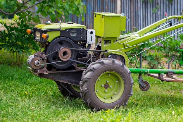 녹색 트레일러가있는 모터 블록. 전통적인 농업 장비 및 농업 개념의 개발.