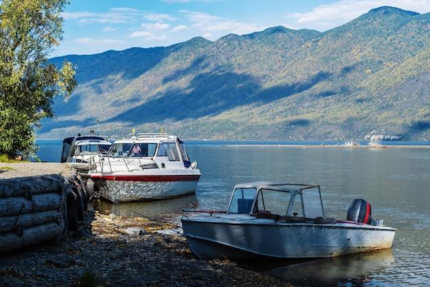 山の湖の岸にある桟橋の近くのモーターボートと遊覧船ロシアアルタイ湖テレツコイェ