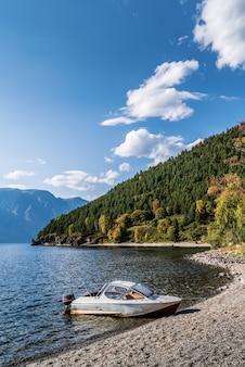 山の湖の岸に係留されたモーターボートロシアアルタイ湖テレツコイェトラクトコルドンチリ