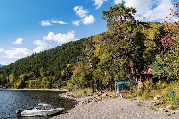 山の湖の岸近くのモーターボート。秋。ロシア、アルタイ共和国、テレツコイ湖