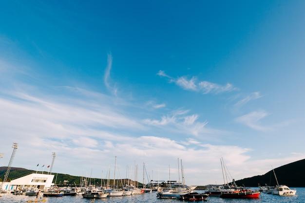 Моторные лодки и яхты на лодочной станции на фоне голубого неба
