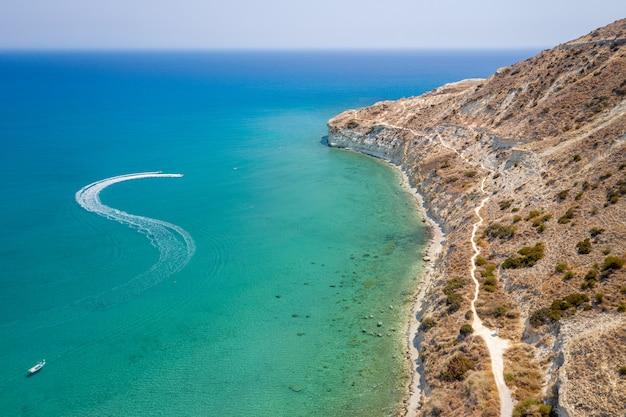 背景の空中写真に地中海のあるキプロスのピッソウリ湾のトレイルを離れるモーターボート