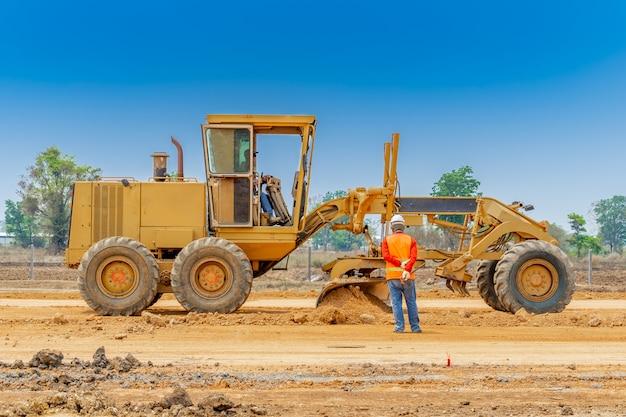 Автогрейдер очищает и выравнивает поверхность строительной площадки, в то время как рабочий контролирует точку уровня