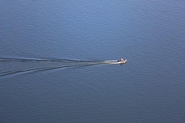 Моторная надувная лодка на фоне синей реки вид сверху текстуры фона воды