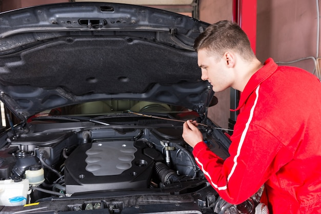 Motor mechanic checking the oil level in a car engine holding the dipstick