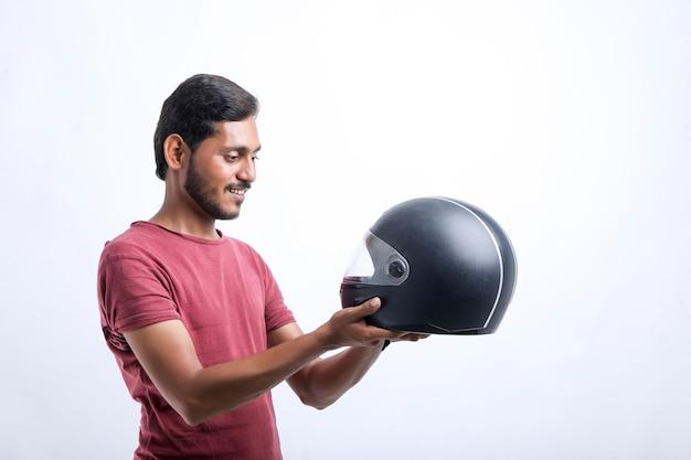 バイクのコンセプト白い背景に黒いヘルメットを持つ若い男。