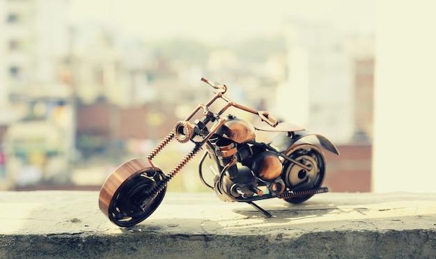背景がぼやけている壁にバイク。ヴィンテージカスタムバイクおもちゃ。