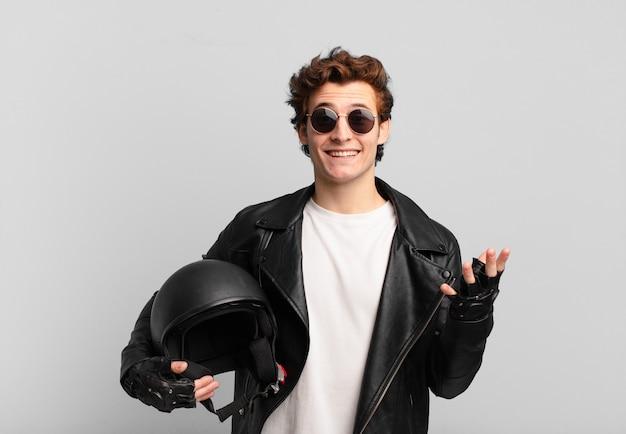 バイク乗りの少年は、幸せで、驚き、陽気で、前向きな姿勢で微笑み、解決策やアイデアを実現している