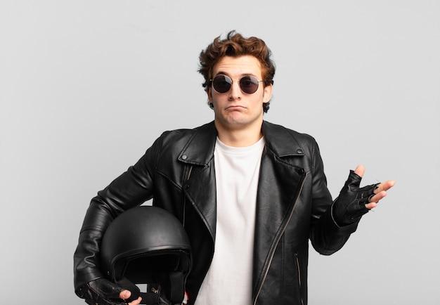 バイク乗りの少年は、当惑して混乱し、疑ったり、重み付けをしたり、面白い表情でさまざまなオプションを選択したり