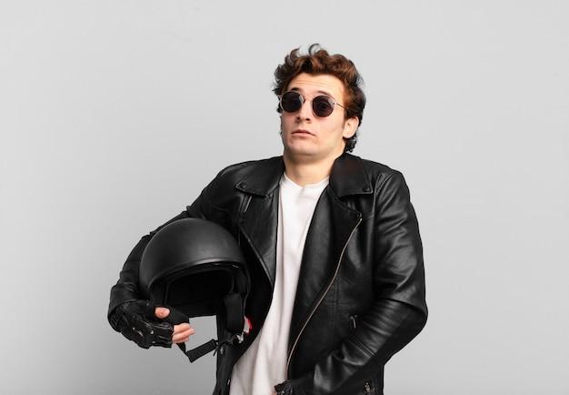 バイク乗りの少年は肩をすくめ、戸惑い、不安を感じ、腕を組み、困惑した表情で疑っている