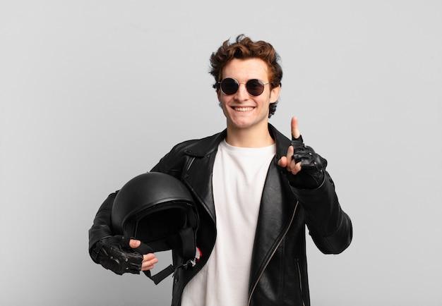 バイクライダーの少年が誇らしげに、自信を持って笑顔でナンバーワンのポーズを勝ち誇って、リーダーのように感じています