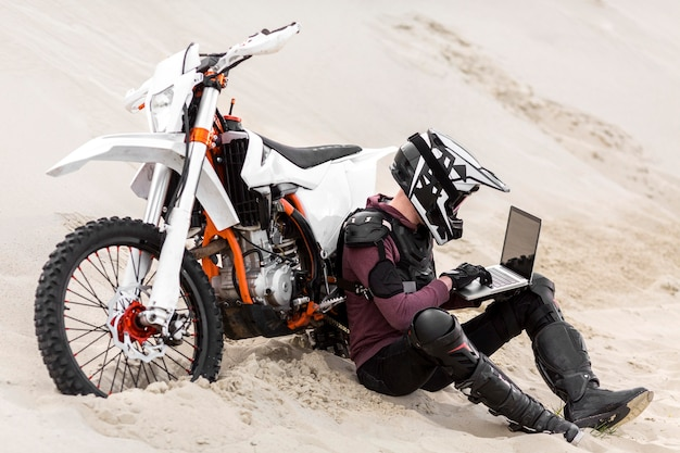 Motorbike rider browsing laptop in the desert