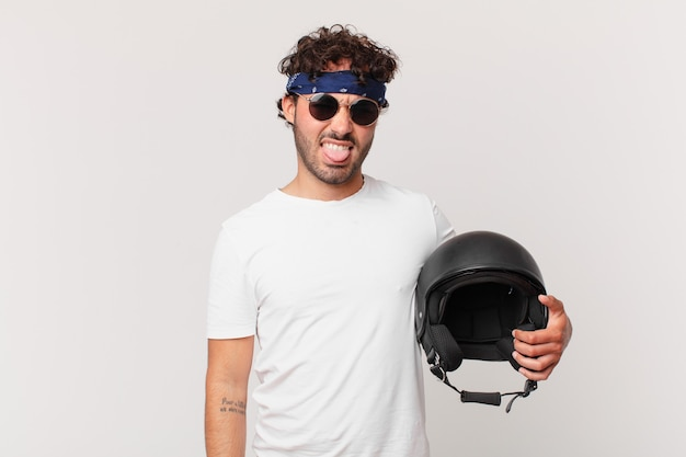 Motorbike rider feeling disgusted and irritated, sticking tongue out, disliking something nasty and yucky