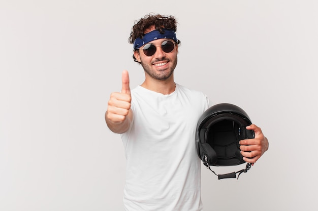 Motorbike rider feeling proud, carefree, confident and happy, smiling positively with thumbs up