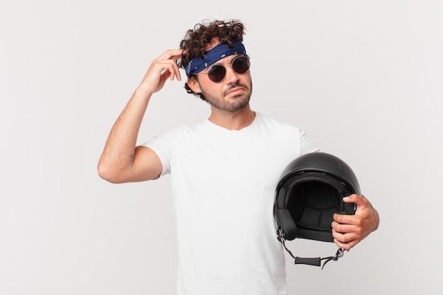 오토바이 라이더는 어리둥절하고 혼란스러워서 머리를 긁적이며 옆을 바라보고 있습니다.