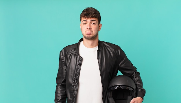 Motorbike rider feeling sad and whiney with an unhappy look, crying with a negative and frustrated attitude