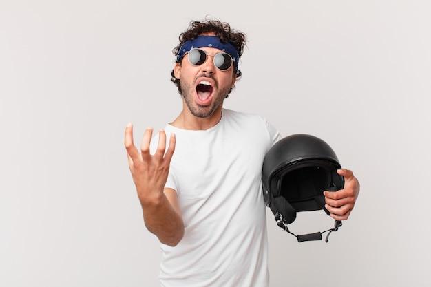 必死になって欲求不満になり、ストレスを感じ、不幸でイライラし、叫び声を上げているバイクライダー