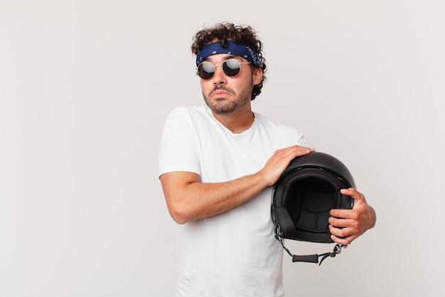 バイクのライダーは肩をすくめ、混乱して不安を感じ、腕を組んで困惑した表情で疑っています