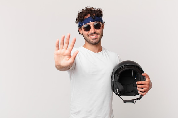 Motorbike rider smiling happily and cheerfully, waving hand, welcoming and greeting you, or saying goodbye