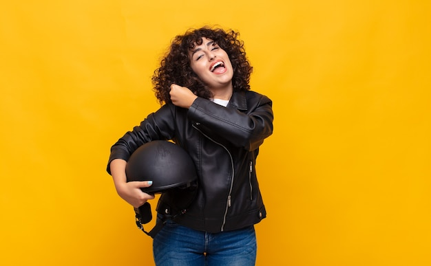 バイクライダーの女性は、挑戦に直面したり、良い結果を祝ったりするときに、幸せで、前向きで、成功し、やる気を感じます