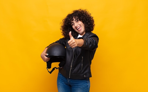 誇り、のんき、自信と幸せを感じ、親指を立てて前向きに笑っているバイクライダーの女性