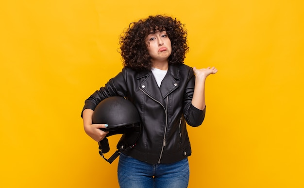 困惑して混乱していると感じているバイクライダーの女性、疑わしい、重みを付けたり、面白い表現でさまざまなオプションを選択したりする