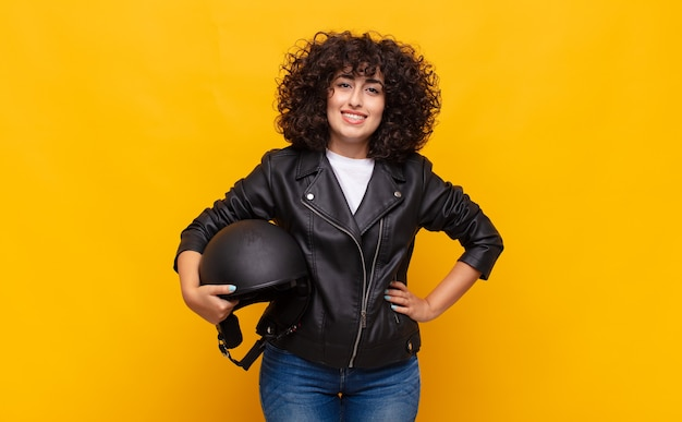 엉덩이와 자신감, 긍정적이고 자랑스럽고 친절한 태도에 손으로 행복하게 웃고있는 오토바이 라이더 여자