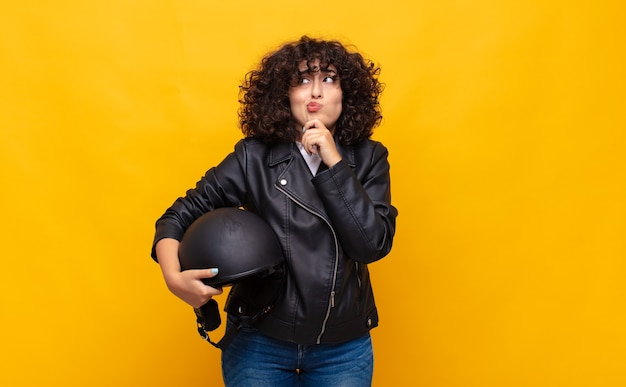 오토바이 라이더 여자 생각, 의심스럽고 혼란 스러움, 다른 옵션으로 어떤 결정을 내릴지 궁금해합니다.
