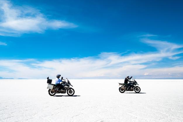 햇빛 살라르 데 우유니 사이에서 오토바이와 자동차를 타고