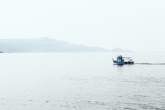 Motorboat on the sea surrounded by mountains enveloped in fog