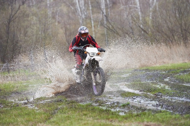 Мотокросс гонщик в грязи трассы во время соревнований на открытом воздухе