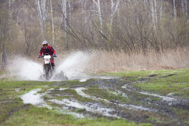 Motorcross rider racing in mud track while moving down country road