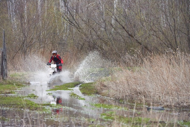 Motorcross rider racing in puddles during competition in natural environment