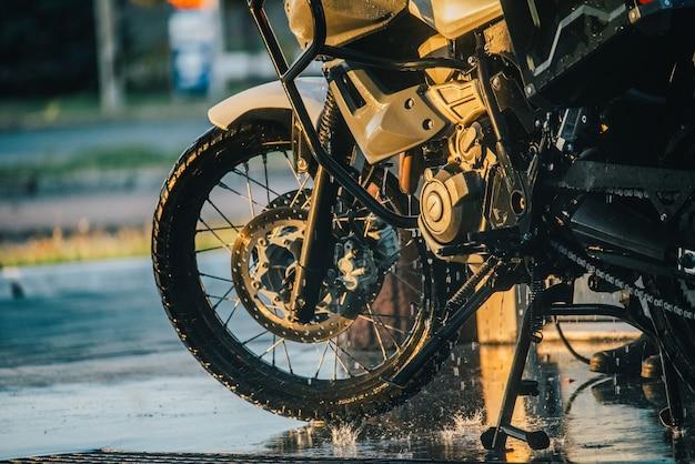 Мойка мотоциклов. серия фотографий, на которых байкер моет свой мотоцикл на автомойке. транспорт