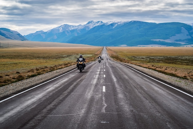 Motorcycle column traveling along the chuysky tract at dawn, landscape with a highway. russia, mountain altai