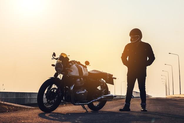 헬멧과 가죽 재킷을 입은 오토바이 운전자가 스포츠 오토바이 옆에 서 있습니다.