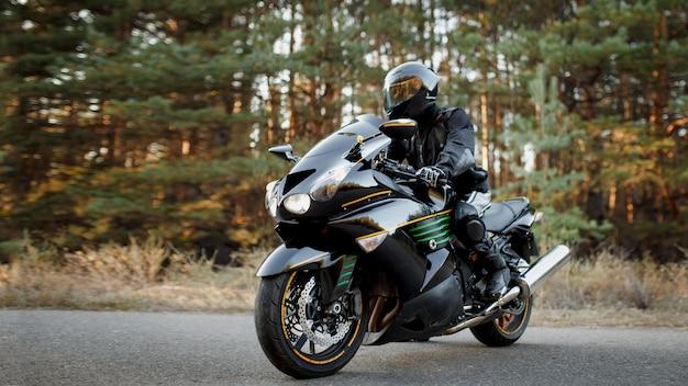 革のスーツを着て、森の背景にアスファルト高速道路で一人でオートバイに座っているオートバイの運転手