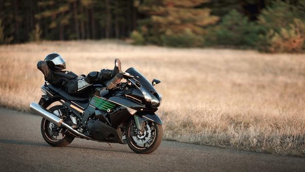 革のスーツを着たオートバイの運転手は、森の背景にアスファルト道路で一人でオートバイに横たわっています