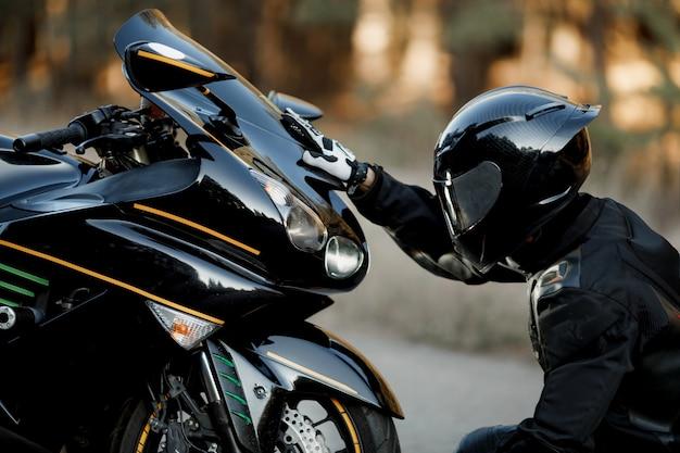 Водитель мотоцикла в кожаном костюме и шлеме сидит один перед мотоциклом и кладет руки на фары.