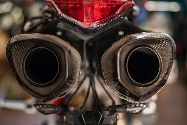 背景がぼやけたオートバイの排気ガスの詳細、エンジン排気ガス