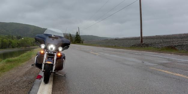 Motorcycle parked on roadside by river, englishtown, cape breton island, nova scotia, canada