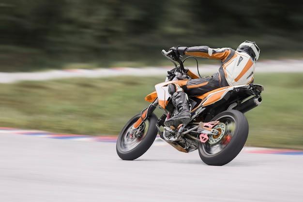 Мотоциклетная практика, наклоняющаяся в быстрый поворот на трассе
