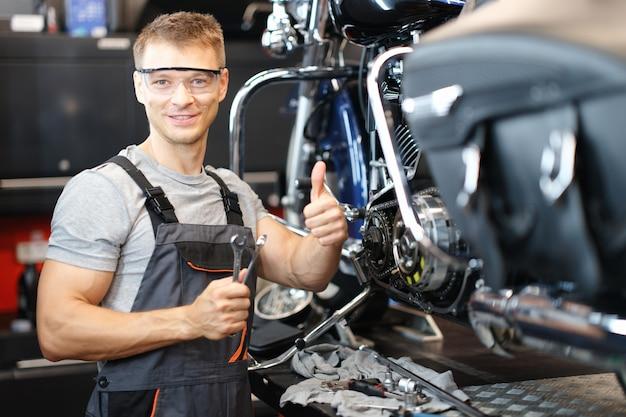 オートバイの修理技術者は、ワークショップに立っている間親指を立てます